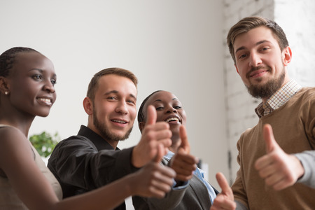 Cheerful business group giving thumbs up Stock Photo