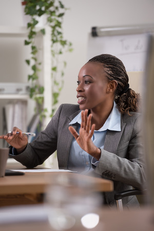 black professional: Emotional businesswoman gesturing during meeting at office