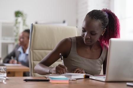 medio ambiente: Mujer de negocios africana que trabajan en el entorno de oficina con ordenador portátil Foto de archivo