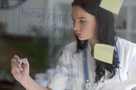 glassboard: Female medical doctor working at clinic office. Writing on glass whiteboard symptoms and test results of her patient to diagnose disease