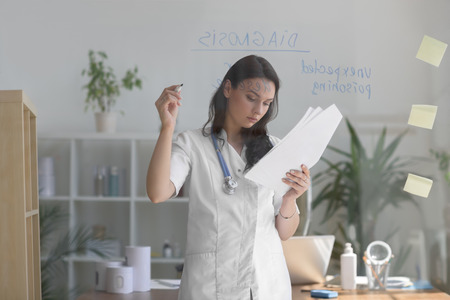 general practice: Female medical doctor working at clinic office. Writing on glass whiteboard symptoms and test results of her patient to diagnose disease