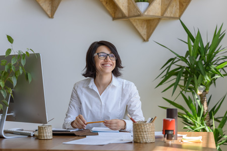 indoors: Woman smiling at office during working day