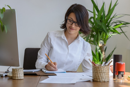 Woman writing at office during working day