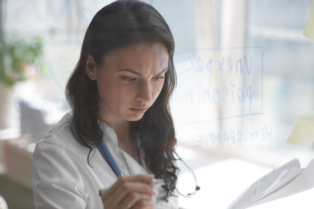 test results: Female medical doctor working at clinic office. Writing on glass whiteboard symptoms and test results of her patient to diagnose disease