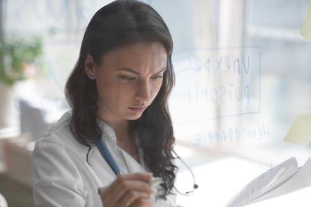 Weibliche Arzt arbeiten im Büro Klinik. Schreiben auf Glas Whiteboard Symptome und Testergebnisse von ihrem Patienten zur Diagnose von Krankheiten Standard-Bild - 42923909