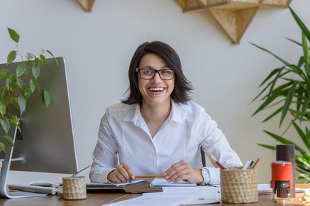 jornada de trabajo: Mujer sonriente en la oficina durante la jornada de trabajo Foto de archivo