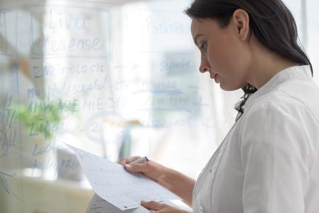 persona escribiendo: Mujer médico que trabaja en la oficina de la clínica. Escribir en la pizarra síntomas vidrio y resultados de pruebas de su paciente para diagnosticar la enfermedad Foto de archivo