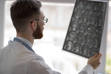 radiographic: Closeup portrait of intellectual man healthcare personnel with white labcoat, looking at brain x-ray radiographic image, ct scan, mri, clinic office background. Radiology department