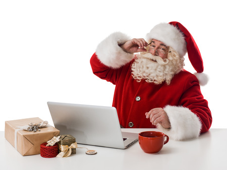 Santa Claus reading children letters and writing responses to them using laptop Closeup Portrait Stock Photo
