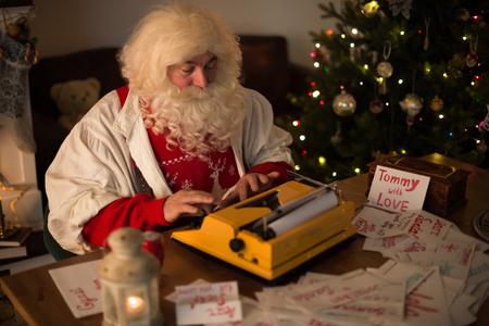 responding: Santa Claus at Home responding to childrens letters Stock Photo