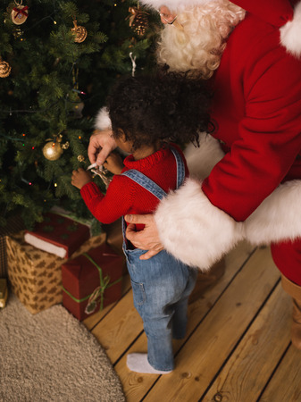 Santa Claus with Child Decorating Christmas Tree Stock Photo