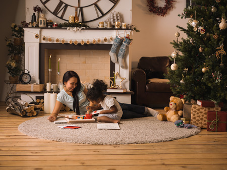 camino natale: Mixed race mother and daughter playing and painting near Christmas tree at home