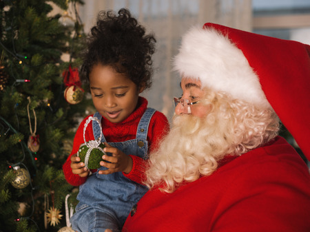 decorating christmas tree: Santa Claus with Child Decorating Christmas Tree Stock Photo