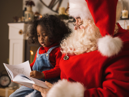 Santa Claus reading a book with cute african child near the fireplace and Christmas tree at home
