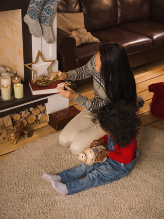Mixed race mother and daughter burning candles near Christmas tree at home