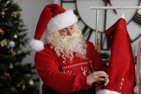 work from home: Santa Claus at Home cleaning his Costume, Preparing for Work