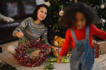 home decorating: Mixed race mother and daughter decorating home near Christmas tree