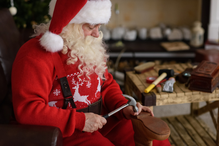 work from home: Santa Claus at Home repairing his Shoes, Preparing for Work Stock Photo