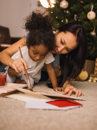 black baby girl: Mixed race mother and daughter playing and painting near Christmas tree at home