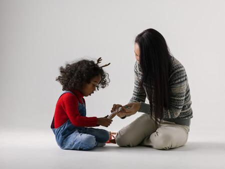 famille africaine: Africaine petite fille jouant avec sa mère pleine longueur asiatique Portrait sur fond uni Banque d'images