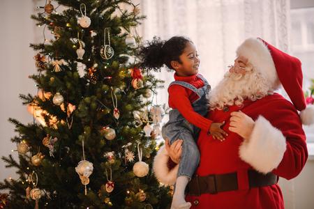 Kerstman het spelen met schattige Afro-Amerikaanse kind thuis Stockfoto
