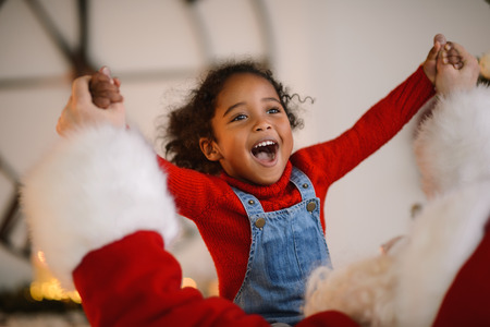 Santa Claus playing with cute african american Child at Home Banco de Imagens