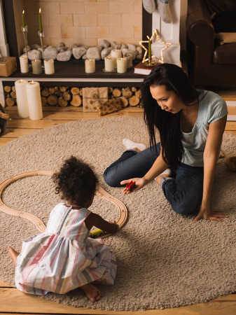 Mixed race mother and daughter playing together near Christmas tree Stock Photo