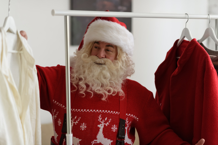 putting: Santa Claus at Home Putting on Costume Stock Photo