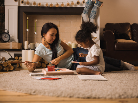 Mixed race mother and daughter playing and painting near Christmas tree at home
