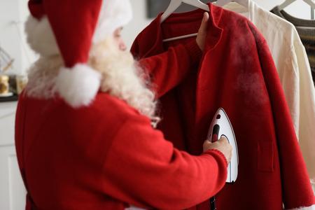 papa noel: Santa Claus en casa de planchado a su vestuario