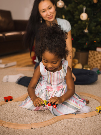 mixed race: Mixed race mother and daughter playing together near Christmas tree Stock Photo