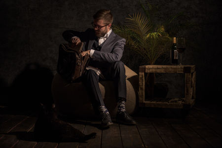 beanbag: Business man Packing something in bag at home while sitting on beanbag