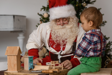 juguetes de madera: Papá Noel con el niño que hace regalos de Navidad y los juguetes en el hogar