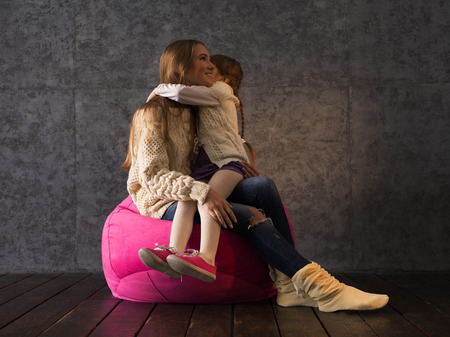 beanbag: Sisters on Beanbag Hugging and having fun together at Home Stock Photo