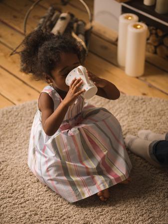 niños sentados: Poco de leche muchacha beber o té en casa Foto de archivo