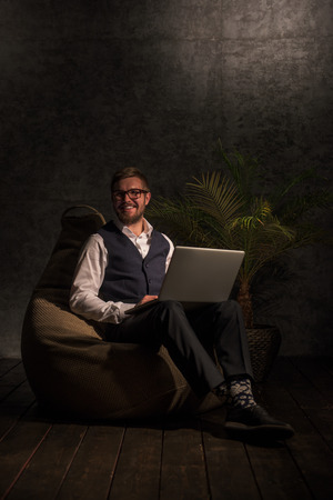 busy beard: Business man Working on Laptop at home or office while sitting on beanbag