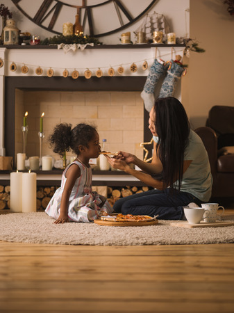 race relations: Mother and Daughter eating pizza at home Stock Photo