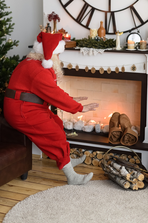 fireplace home: Santa Claus Warming near Fireplace at Home Stock Photo