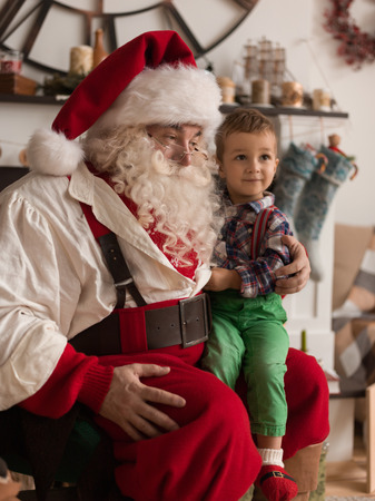 Santa Claus with Child discussing Christmas Wish at Home