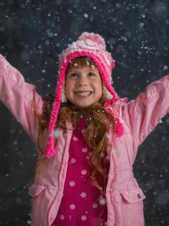Little girl having fun under snow outside Standard-Bild