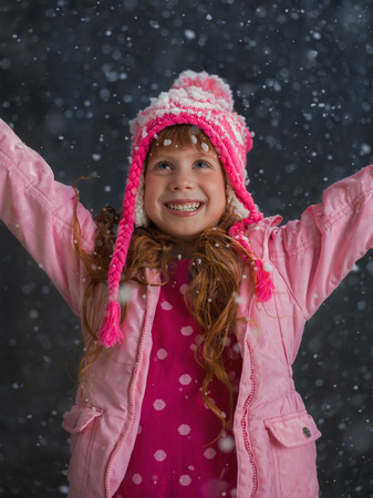 Little girl having fun under snow outside Imagens