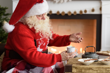 Santa Claus Drinking Coffee with Marshmallow near Fireplace at Home
