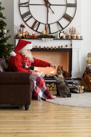 Kerstman Warming Feeding zijn Kat thuis Stockfoto