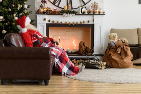 Kerstman Warming buurt van open haard thuis Stockfoto