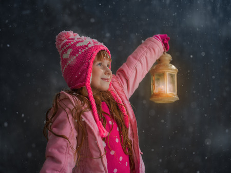 Little girl having fun under snow outside and lighting her way with lantern
