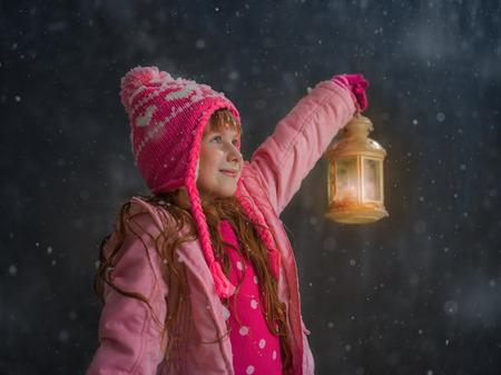 Meisje dat pret onder de sneeuw buiten en het aansteken van haar weg met lantaarn