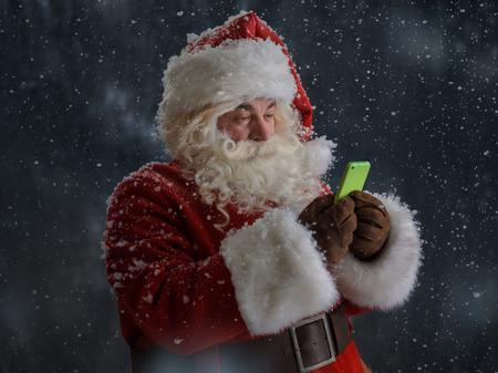 Foto van Santa Claus met behulp van mobiele telefoon buitenshuis onder sneeuw