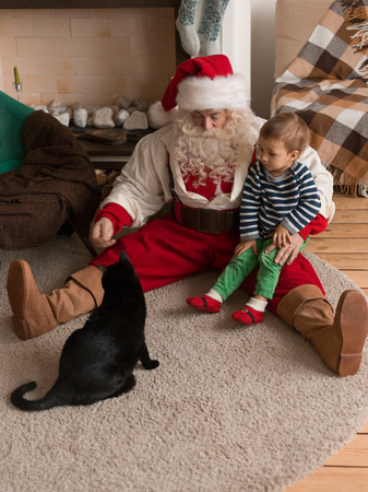 Santa Claus Playing at Home with Child and Cat Standard-Bild