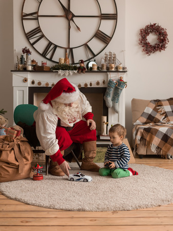 Santa Claus with Child Playing Together at Home Standard-Bild