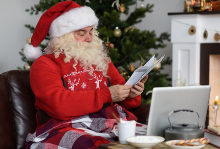 Kerstman Werken in de buurt van de kerstboom thuis. Reading kinderen brieven
